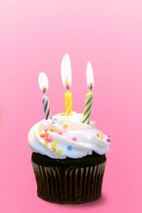 Chocolate Cupcake With Burning Candles on Pink Background
